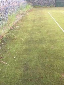 A worn synthetic tennis court before our professional maintenance services.