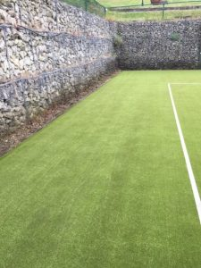 A rejuvenated synthetic tennis court after our professional maintenance services.